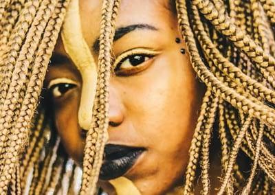black woman with black lipstick and blond braids.